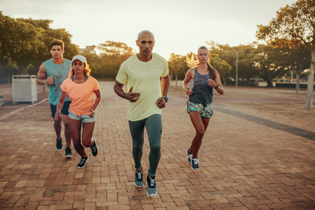 Fit young man runs with friends. Group of young people doing running workout together in evening.