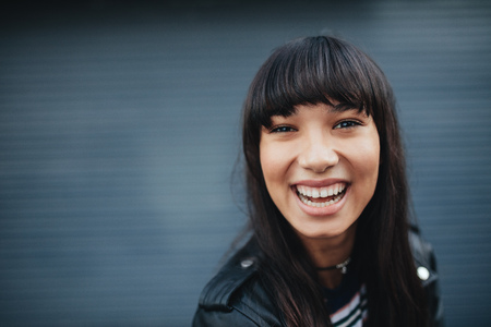Close up portrait of young woman laughing against gray background. Beautiful hispanic female model having fun outdoors.