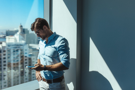 formals: Young businessman looking at mobile phone standing beside a window. Man dressed in formals standing near window of highrise office building overlooking the cityscape.