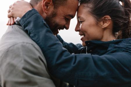 Close-up zijportret van een jong koppel in liefde om elkaar liefdevol te kijken en hun hoofd op elkaar te leunen.