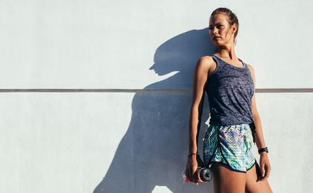Portret die van jonge vrouw zich in openlucht met waterfles bevinden die weg tegen een muur kijken. Vrouwelijke atleet ontspannen na training. Stockfoto