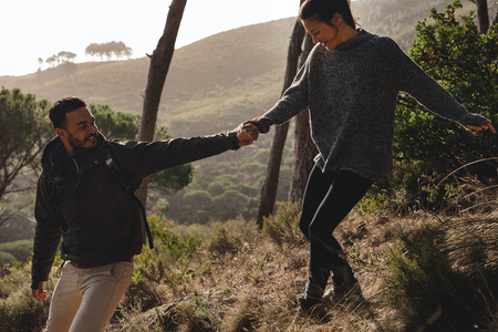 Outdoor shot of young couple enjoying on their hiking trip, walking down the mountain trail. Male hiker helping his girlfriend downhill in the countryside.