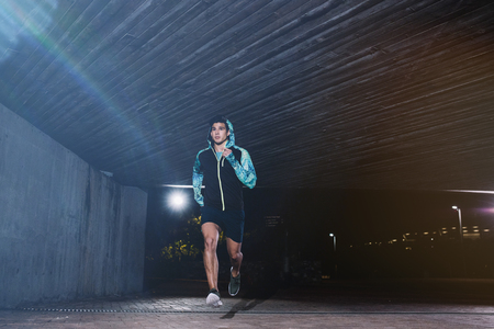 Full length shot of a young man jogging at night. Fit male athlete running under a bridge. Stok Fotoğraf