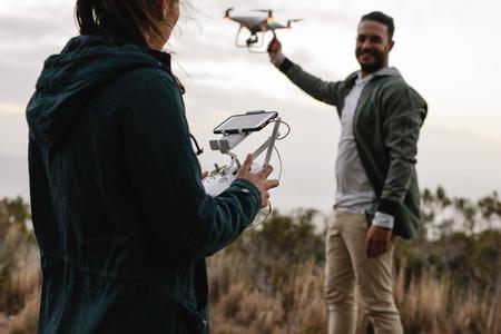 リモート コントロールと田舎の飛行ドローンを抱きかかえた女性。若いカップルの田園地帯での飛行ドローン。 写真素材