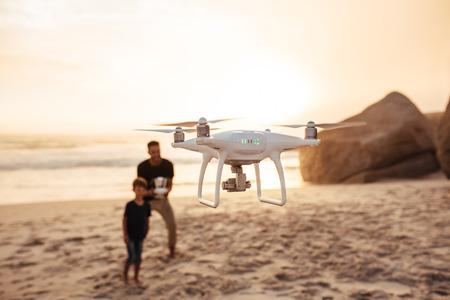 Drone wordt bestuurd door vader en zoon aan de kust. Vader en zoon op de vliegende hommel van de de zomervakantie op strand. Focus op drone, met vader en zoon op achtergrond.