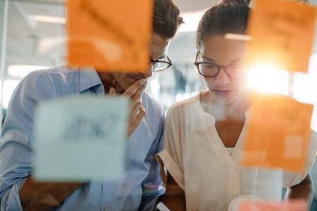 두 비즈니스 전문가 스티커 메모와 유리 벽 뒤에 서 논의 하 고. 동료 사무실에서 새로운 사업 아이디어에 브레인 스토밍.