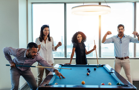 involving: Young men and woman playing billiards at office after work. Business colleagues involving in recreational activity after work. Stock Photo