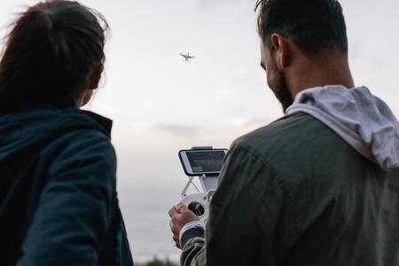 若いカップルの側に立って一緒に屋外無人操作用のリモコンを抱きかかえたの背面ビュー ショット。男と女の飛行ドローン屋外。 写真素材