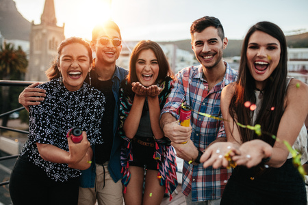 Smiling young people throwing confetti on a rooftop party. Best friends enjoying the party together with confetti.