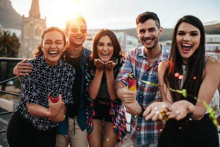 젊은 사람들이 옥상 파티에 색종이 조각을 던지고 웃고. 색종이 함께 파티를 즐기는 가장 친한 친구. 스톡 콘텐츠