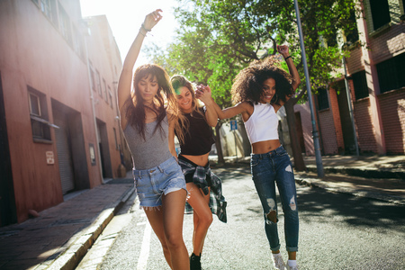 Outdoor shot of beautiful young women having fun on city street. Multiracial female friends enjoying a day out in the city.