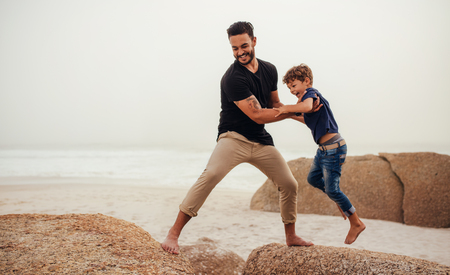 Shot of father helping his son to jump over the rock on the beach. Young man and little boy having fun at the rocky beach. Stock Photo
