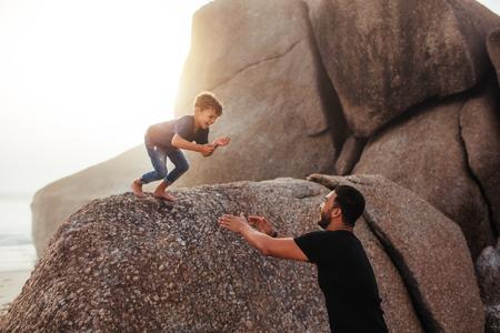 Disparo al aire libre de padre e hijo se divierten en las vacaciones de verano en la playa. Niño feliz saltando en los brazos de su padre de una roca. Foto de archivo - 80065051