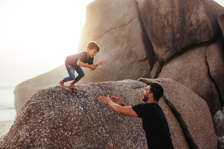 Foto ao ar livre de pai e filho se divertindo nas férias de verão na praia. menino feliz pulando nos braços de seu pai de uma rocha. Foto de archivo - 80065051