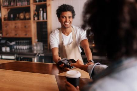 Cliente femminile facendo il pagamento attraverso il telefono cellulare al banco in caffè con giovane uomo. Barista che tiene macchina di lettura della carta di credito davanti alla femmina cliente con il telefono delle cellule. Archivio Fotografico - 80065081
