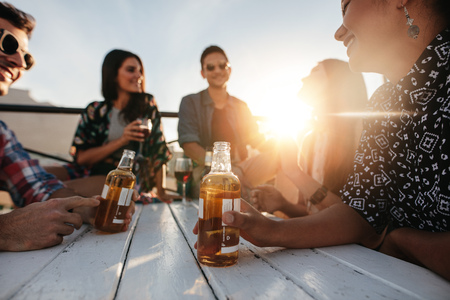 Group of young people sitting around a table with drinks. Young men and women having rooftop party with focus on beer bottle. Stock Photo