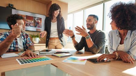 Jong en creatief start-up team dat ideeën in vergaderzaal bespreekt. Groep multi-etnische mensen tijdens commerciële vergadering. Stockfoto
