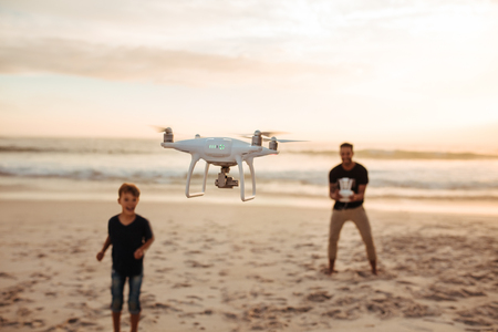 Father and son operating the drone by remote control at the sea shore. Young man with little boy flying drone at the beach during summer vacation. Focus on drone, with father and son in background.