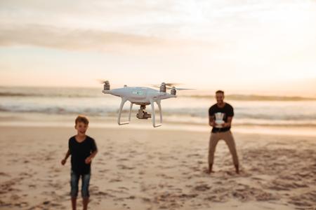 Vater und Sohn betreiben die Drohne per Fernbedienung am Meer. Junger Mann mit kleinen Jungen fliegen Drohne am Strand während Sommerurlaub. Fokus auf Drohne, mit Vater und Sohn im Hintergrund.