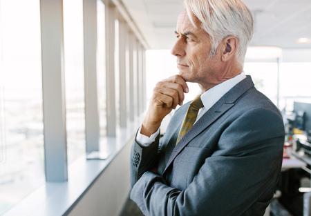 Zijaanzicht van rijpe zakenman wordt geschoten die zich naast bureauvenster bevinden die buiten en met hand op kin denken kijken. Senior professioneel denken voor oplossingen.