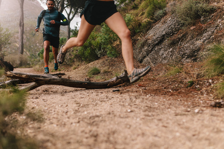 Young people running on country trail path. Low angle shot of runners exercising on rural dirt path.