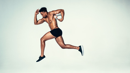 Side view shot of young man training with rugby ball. Male model with muscular build running with rugby ball over grey background. Фото со стока