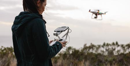 リモコンで飛行ドローンをナビゲートする若い女性。飛行ドローンと写真を撮る田舎の女性。