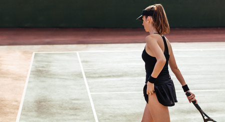 Female tennis player on the court. Sports woman playing a match on tennis court.