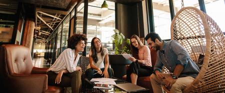 ビジネス チームは新しいプロジェクトに取り組んでいると笑顔します。男性と女性のプロジェクトの議論のため近代的なオフィスで一緒に座ってい