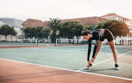 Young healthy girl doing stretching exercises on tennis court. Sportswoman doing warmup workout outdoors. Фото со стока