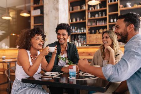 若いお友達とレストランで素晴らしい時間を過ごしてします。笑みを浮かべてコーヒー ショップに座っている若い人たちの多民族のグループ。
