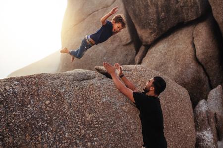 小さな男の子が彼の父の腕の中に岩から跳躍の屋外撮影。父と息子のビーチで夏の休日を楽しんでします。