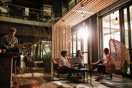 Bedrijfsmensen die in sociale ruimte in modern bureau zitten. Jonge mannen en vrouwen nemen een pauze van het werk.