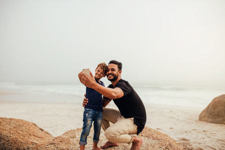 Shot of father and son taking selfie at the rocky beach. Young man with little boy making self portrait using smart phone at the sea shore. Stock Photo