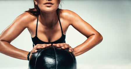 Cropped shot of young woman doing push up on medicine ball. Close up of fitness female exercising with a medicine ball on grey background.