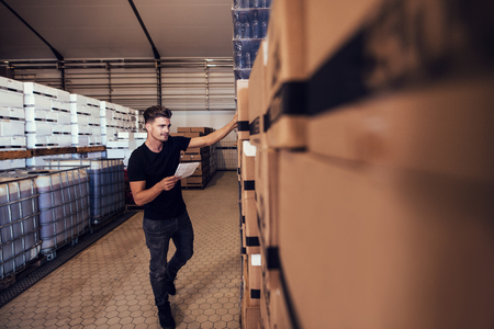 Young man taking the stock of packaged beer boxed in warehouse. Warehouse manager taking finished goods inventory at brewery.