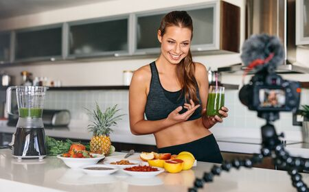 tripod mounted: Smiling woman preparing a healthy breakfast with fruits and vegetables. Young lady holding glass of green juice at the kitchen table looking at a camera mounted on tripod.