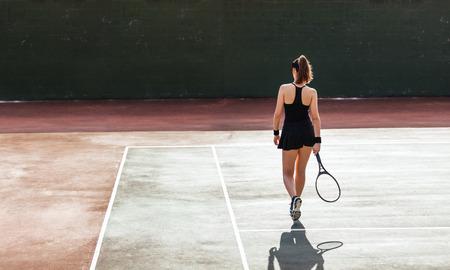법원에 여성 테니스 선수의 전체 길이 후면보기. 스포츠 여자 테니스 코트에서 재생입니다.
