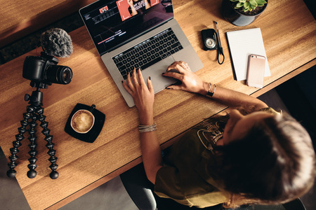 Top view of female vlogger editing video on laptop. Young woman working on computer with coffee and cameras on table.