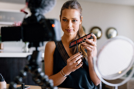 Young lady holding a makeup palette while recording her video. Woman making a video for her blog on cosmetics.