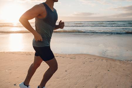 海岸でワークアウト フィット若い男性ランナーのショットをトリミングしました。朝のビーチに沿って実行している若い男。