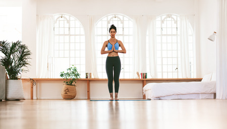 Full length portrait of fit young woman standing with her hands joined at home. Fitness female meditating indoors. Stock Photo