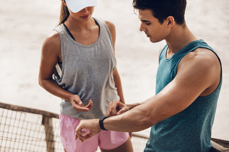 Young man showing heart rate monitor watch to woman during break. Fitness couple checking their workout performance on a smart watch.