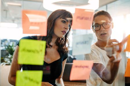 아시아 사업가 그녀의 동료 표시 스티커 메모 벽에 아이디어. 창조적 인 전문가들은 새로운 비즈니스 아이디어에 대해 브레인 스토밍합니다.