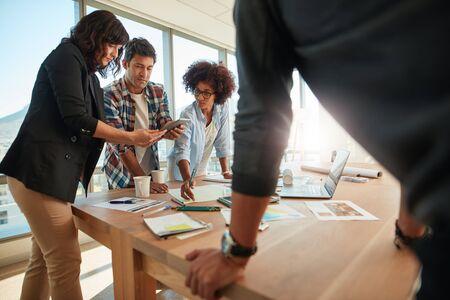 創造的な職場でテーブルを囲んで一緒に働く若いビジネス人々 のグループ。新しいプロジェクトに取り組む創造的な専門家のチーム。 写真素材 - 80860787