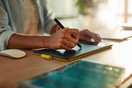 stylus pen: Closeup of womans hand using a graphic tablet and stylus pen. Female designer working at her desk Stock Photo
