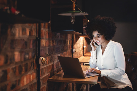 working office: Happy businesswoman working late on laptop and talking on mobile phone in office. African female entrepreneur using laptop and cell phone while sitting at a table. Stock Photo