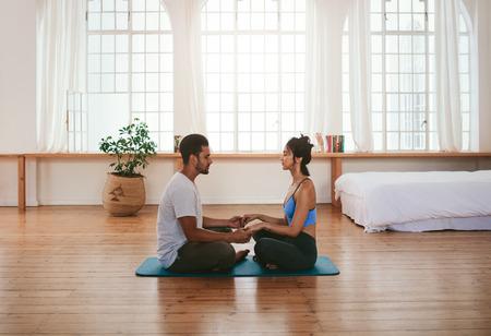 自宅でヨガをしている美しい若いカップルの側面図です。彼らは一緒に手を繋いでいるヨガのマットの上に座っています。