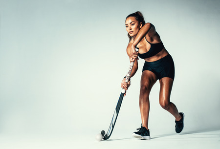 Full length of woman hockey player dribbling ball on grey background. Hispanic female playing hockey in studio.