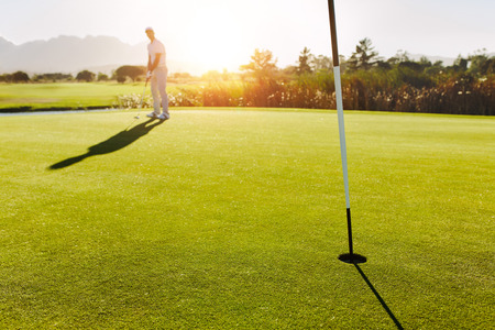 Golf hole and flag in the green field with player in background. Professional male golfer putting the ball. 스톡 콘텐츠